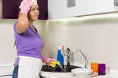 Housewife straightening her cap as she works — Stock Photo