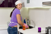 Smiling cook washing the dishes in the kitchen — Stock Photo
