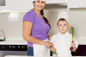 Smiling mother and son in chefs outfits — Stock Photo
