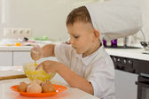 Cute young boy chef whipping the eggs — Stock Photo