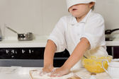 Little child baking in a chefs toque — Stock Photo
