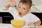 Young boy taking a taste of the cake mix — Stock Photo