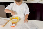 Young boy baking adding flour to the mixture — Stock Photo