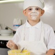 Постер, плакат: Messy young boy preparing to bake