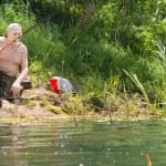 Elderly shirtless man fishing on a lake — Stock Photo #48517545