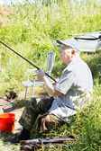 Elderly disabled man fishing on a river bank — Stock Photo
