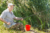 Senior angler fishing from a reed bank — Stock Photo