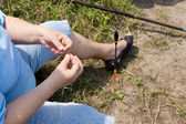 Woman threading bait onto her hook while fishing — Stock Photo