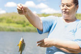 Middle aged woman holding up a fish — Stock Photo