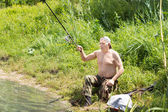 Disabled man casting his fishing rod — Stock Photo
