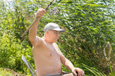 Senior fisherman dangling a fish on his line — Stock Photo