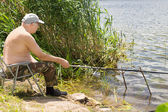 Elderly man fishing on a freshwater lake — Stock Photo