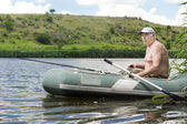 Senior man fishing from a rubber dinghy — Stock Photo
