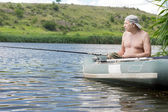 Senior man relaxing fishing from a dinghy — Stock Photo