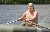 Smiling man enjoying a row in a rubber dinghy — Stock Photo