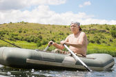 Senior man rowing an inflatable dinghy on a lake — Stock Photo