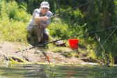 Man fishing at the edge of a lake — Stock Photo