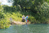 Elderly couple fishing on a quiet freshwater lake — Stock Photo