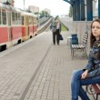 Woman sitting on a bench in a railway station — Stock Photo #49168625