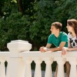 Young couple leaning on a bridge parapet — Stock Photo #49168671