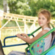 Smiling little girl sitting on a fairground ride — Stock Photo #49168965