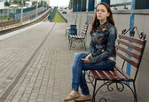 Young woman sitting on a roadside bench — Stock Photo