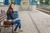 Woman waiting at a railway station for transport — Stock Photo