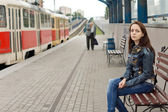 Woman sitting on a bench in a railway station — Stock Photo