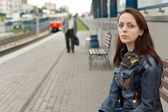 Lonely girl waiting in an urban railway station — Stock Photo