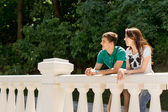 Young couple leaning on a bridge parapet — Stock Photo