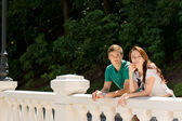Happy young couple leaning on a balustrade — Stock Photo