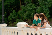 Young couple standing chatting on a bridge — Stock Photo
