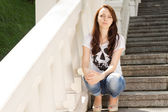 Attractive young woman sitting on steps — Stock Photo