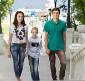Attractive couple walking with a cute little girl — Stock Photo