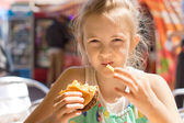 Girl eating French fries and a hamburger sandwich — Stock Photo