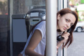 Young woman looking outside the telephone booth — Stock Photo