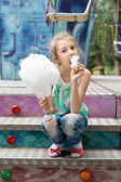 Young girl relishing a stick of candy floss — Stock Photo