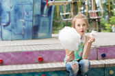 Laughing little girl eating candy floss at a fair — Stock Photo