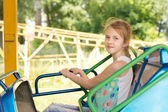 Sorridente ragazzina seduta su un giro in fiera — Foto Stock