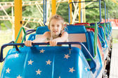 Little girl sitting on a fairground ride — Stok fotoğraf