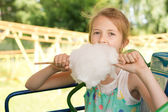 Cute young girl tucking into a ball of candy floss — Stock Photo