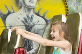 Excited little girl enjoying a ride at the funfair — Stock Photo