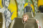 Little girl peering between seats on a fairground — Stockfoto