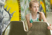 Sulky little girl sitting on a fairground ride — Stock Photo