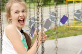 Funny cute girl screaming in the swing ride — Stock Photo