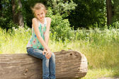 Cute coy little girl sitting on a log in woodland — Stock Photo