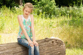 Little girl sitting in woodland on a log — Stock Photo