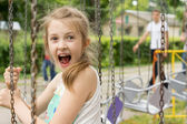 Excited little girl on a ride at the fairground — Stock Photo