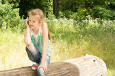 Cute observant little girl on a log — Stock fotografie
