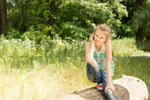 Little girl sitting on a log thinking — Stock Photo